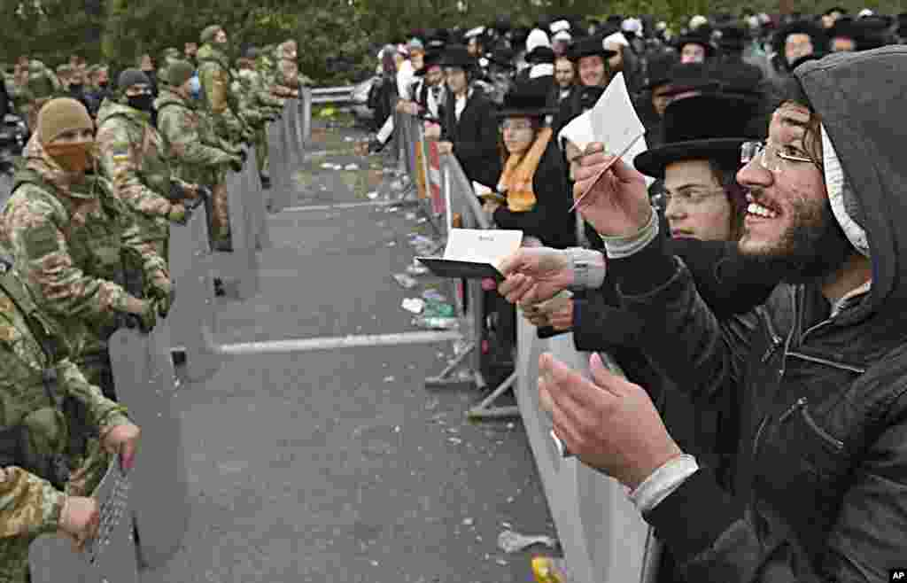Hasidic Jewish pilgrims gather in front of Ukrainian border guards at the Novaya Guta checkpoint near Novaya Guta, Belarus, on September 18. Ukrainian officials said that thousands of Hasidic Jewish pilgrims stuck on the Ukrainian border due to coronavirus restrictions have started turning back. About 2,000 ultra Orthodox Jewish pilgrims traveled to Belarus's border with Ukraine in hope of traveling to the Ukrainian city of Uman to visit the grave of an important Hasidic rabbi who died in 1810. (AP)