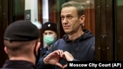 Russian opposition leader Aleksei Navalny shows a heart symbol during a court hearing in Moscow on February 2.