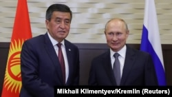Президент России Владимир Путин (справа) пожимает руку президенту Кыргызстана Сооронбаю Жээнбекову во время встречи в Сочи 28 сентября.
