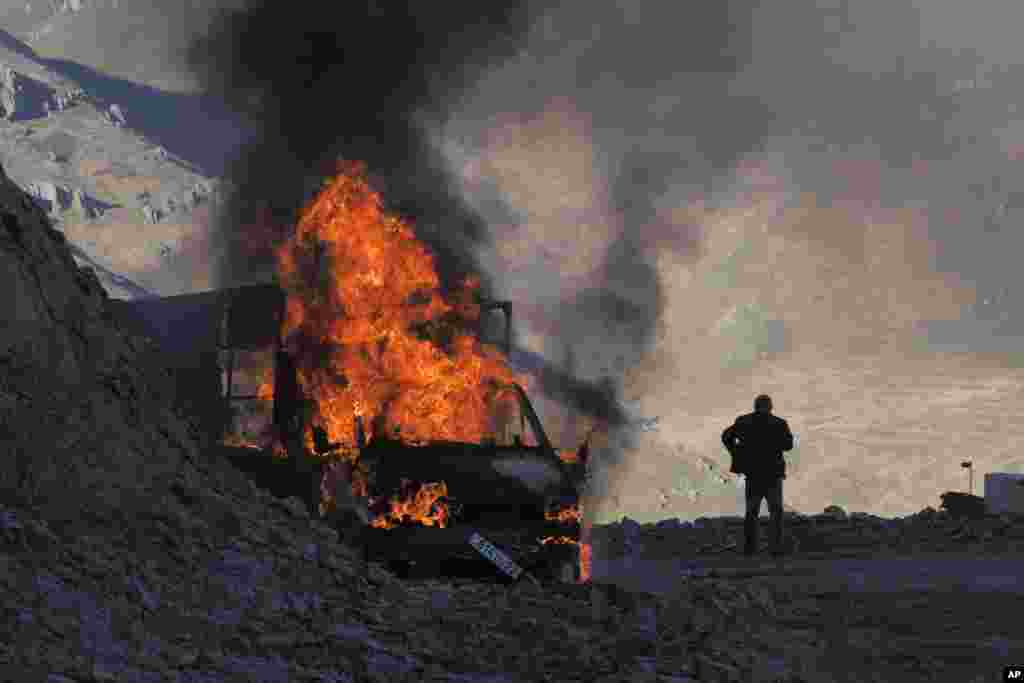 A man stands near a burning car on a mountain road between Nagorno-Karabakh and Armenia as heavy fighting continued around the town of Shushi/Susa on November 8.