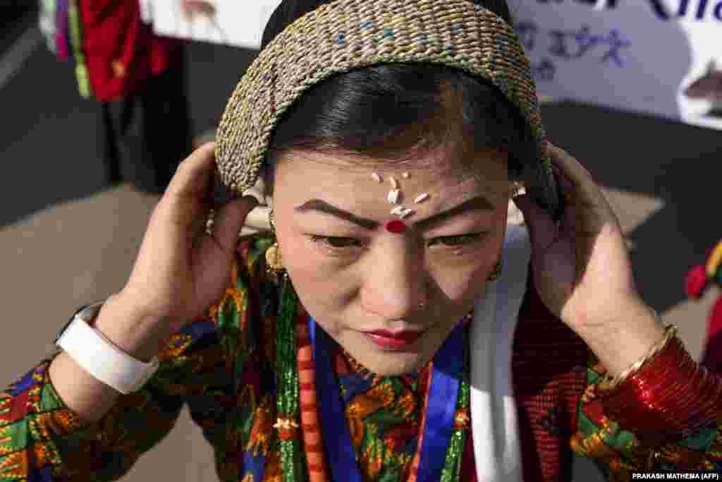 """Egy nő rendezi a fejdíszét a nepáli gurung törzsből, a """"Tamu Lhosar"""" nevű újévi ceremónia előtt Katmanduban 2019. december 31-én."""