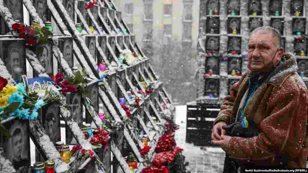 Чоловік запалює лампадку біля Меморіалу Небесної сотні