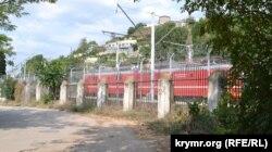 Железнодорожный вокзал по периметру окружен забором с колючей проволокой. Вид со стороны Южной бухты