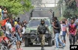Petionville rendőrállomás mellett nézik a járókelők az elfogott gyanúsítottakat a rendőrautóban, 2021. július 8-án.