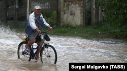 Мужчина едет на велосипеде по затопленной улице в Керчи | Крымское фото дня