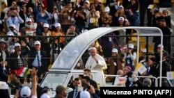 Папата Франциск ги благословува луѓето додека пристигнува со возилото на стадионот Франсо Харири во Ербил, 7 март 2021 година