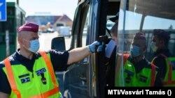 Egy belépő gépjármű utasainak hőmérsékletét ellenőrzi egy rendőr a hegyeshalmi határátkelőnél 2020. szeptember 5-én.