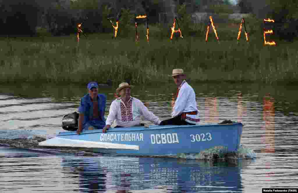 "People ride in a boat during Ivana-Kupala celebrations. The letters on fire in the background read ""Kupale."" The name of the holiday comes from John the Baptist (John or Ivan), while ""kupala"" presumably refers to baths or bathing."