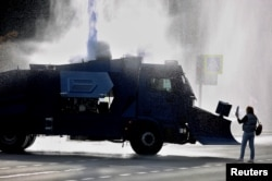 An opposition supporter stands next to a police water cannon during a rally in Minsk on October 4.
