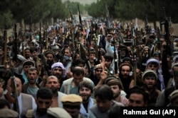 Militiamen join Afghan security forces during a gathering in Kabul on June 23.