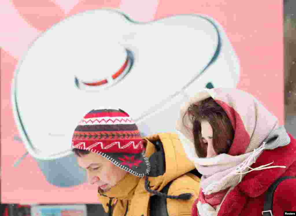 Пара проходить повз магазин електроніки, прикрашений до Дня святого Валентина в морозний зимовий день в центральній частині Києва, Україна, 12 лютого 2021 року