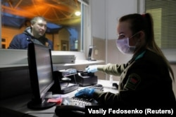 A Belarusian border guard wears a face mask and gloves to protect herself from the coronavirus early in the pandemic. Belarus closed off its borders to foreigners on November 1.