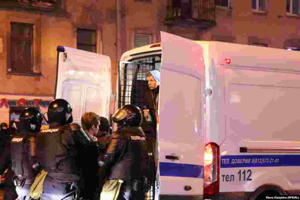 St. Petersburg security forces load detainees into a police van. More than 10,000 people across Russia have been detained at protests in support of Navalny since January.