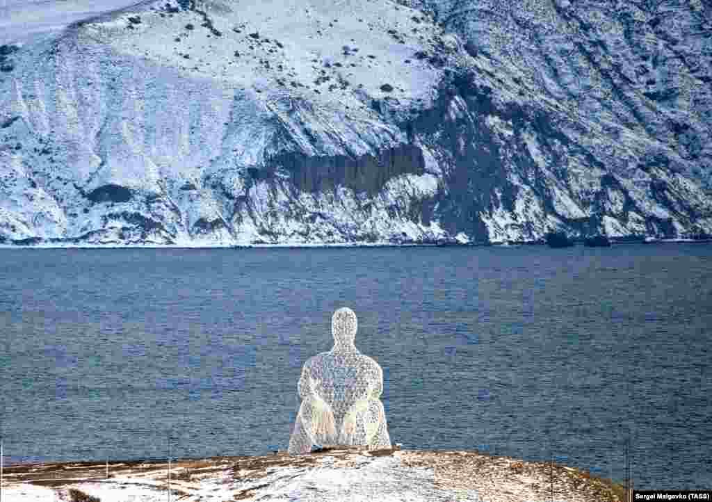 Инсталляция в виде человека, сидящего на берегу моря, в бухте Капсель