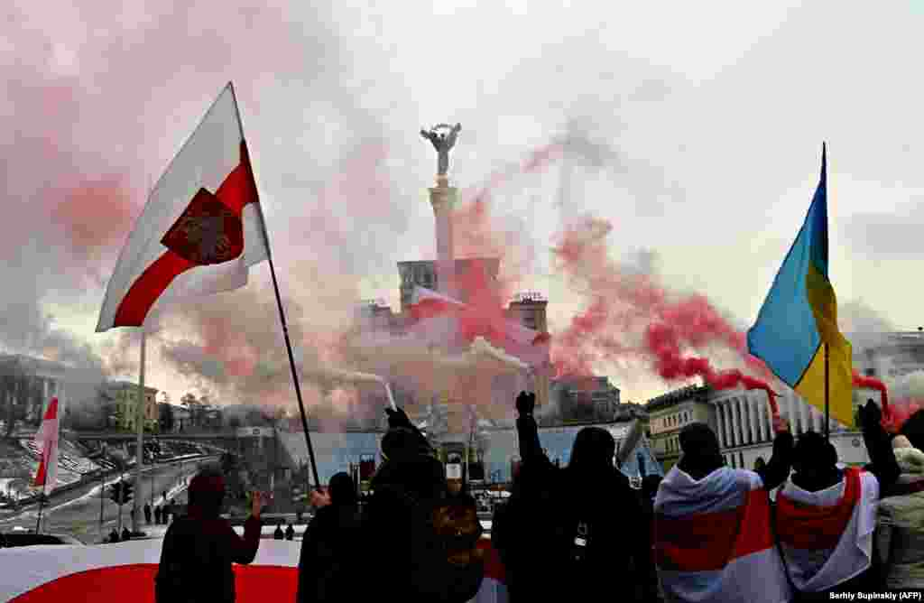 Members of the Belarusian diaspora and Ukrainian activists hold up white and red flares during a rally in support of anti-government protesters on the international Day of Solidarity with Belarus in the center of Kyiv on February 7. (AFP/Sergei Supinsky)