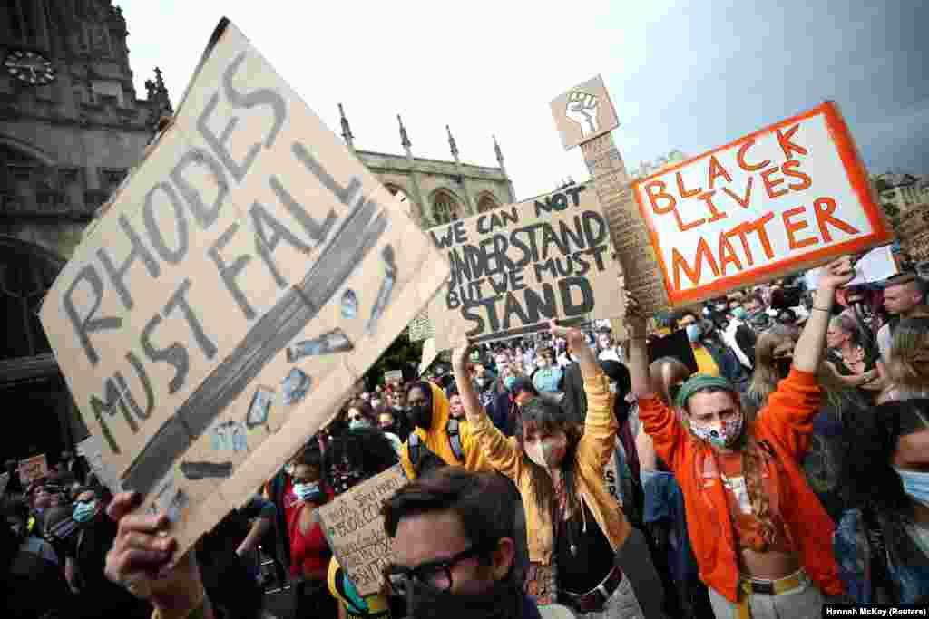 Демонстранти з плакатами протестують із вимогами зняти пам'ятник британському імперіалістові Сесілю Родсові біля Орієл-коледжу, однієї зі складових Оксфордського університету, в Оксфорді в Великій Британії 9 червня 2020 року. Тисячі людей вимагали зняти цей пам'ятник як, за словами з листа групи членів міської ради, несумісний із антирасистською позицією міста.