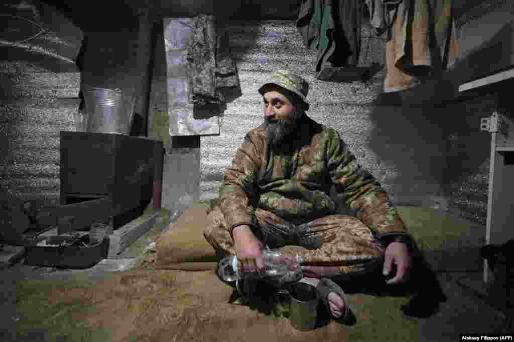 A Ukrainian serviceman rests in a dugout on the front line near Mariupol in eastern Ukraine. (AFP/Aleksei Filippov)