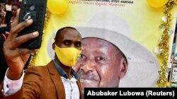 Pristalica Yowerija Musevenija slika se ispred plakata s njegovim likom u Kampali, Uganda (12. januar 2021.)