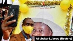 Симпатизер на претседателот Мусевени се слика пред постер со неговиот лик