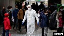 Специалист в защитной одежде и прохожие в защитных масках на городской улице во время пандемии коронавируса. Чешская Республика.