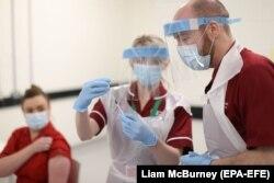Punëtorët shëndetësorë duke u përgatitur që t'ia administrojnë vaksinën kundër COVID-19 një qytetareje.