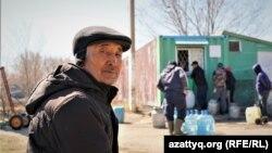 Житель села Приречное Жанбай Габдол ждет очереди за питьевой водой. Акмолинская область, 21 апреля 2021 года.
