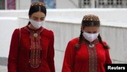 Жени със защитни маски, заснети на улицата в Ашхабад.