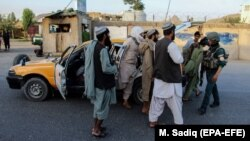 Afghan security officials stop people at a checkpoint in Kandahar on June 8.