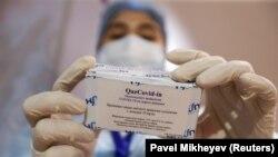 Медработник показывает коробку с флаконами с вакциной QazCovid-in (QazVac) в центре вакцинации. Алматы, 27 апреля 2021 года.