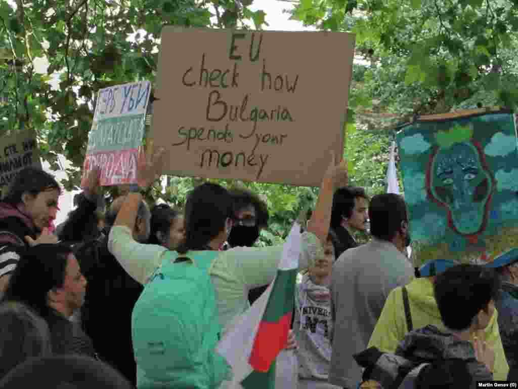 """Протестираща с плакат, призоваващ: """"ЕС, провери как България харчи парите ти""""."""