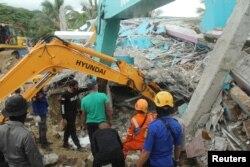 Túlélők után kutatnak egy összedőlt kórháznál Mamujuban, 2021. január 15-én.