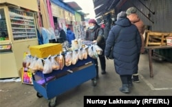 Продающая горячий чай и булочки женщина. Алматы, 24 декабря 2020 года.