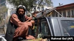 Вооруженный боевик «Талибана» напротив главных ворот президентского дворца в Кабуле. 16 августа 2021 года