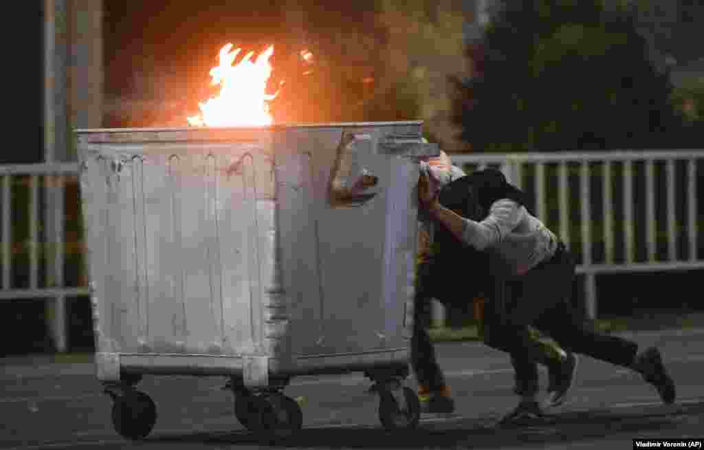 Protesters push a burning trash can towards riot police in Bishkek on October 5.