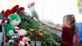 Девочка возлагает цветы у школы в Казани
