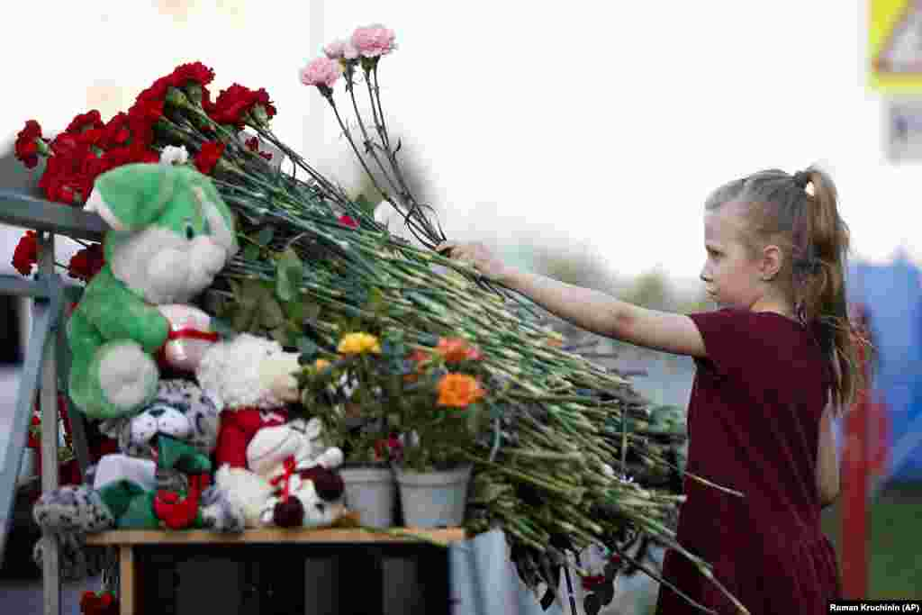 A girl lays flowers near a school after the shooting in Kazan on May 11.