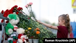 A young girl lays flowers at an impromptu shrine to victims of a deadly school shooting that took place in Tatarstan's capital, Kazan, earlier this week.
