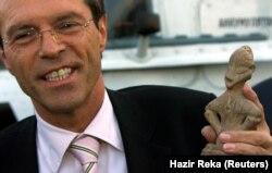 """Ish-shefi i Misionit të Kombeve të Bashkuara të Kosovës, Michael Steiner, duke mbajtur në dorë """"Hyjneshën në Fron"""", që u kthye nga Serbia. Ky artefakt, që është zbuluar afër """"Tjerrtores"""" në Prishtinë, është edhe simboli i Komunës së Prishtinës."""