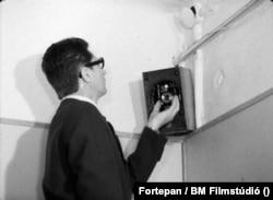1962: Rejtett fényképezőgép telepítése egy irodai rádió hangszórójába. Képkocka a Belügyminisztérium Filmstúdiójának az álcázás technikai részleteit oktató filmjéből.