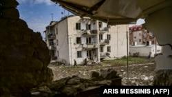 Бүлінген үйлердің арасынан өтіп жатқан ер кісі. Степанакерт қаласы, Таулы Қарабақ, 8 қазан 2020 жыл.