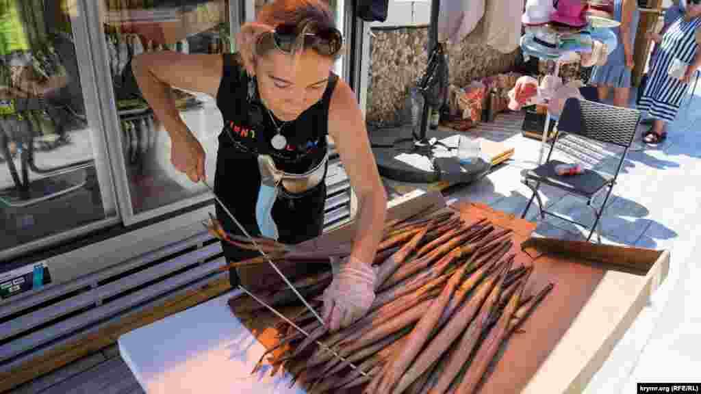 Продавець нанизує копчену рибу-флейту на вітринні штирі. Ціна однієї такої флейти – 200-300 рублів (75-112 грн)