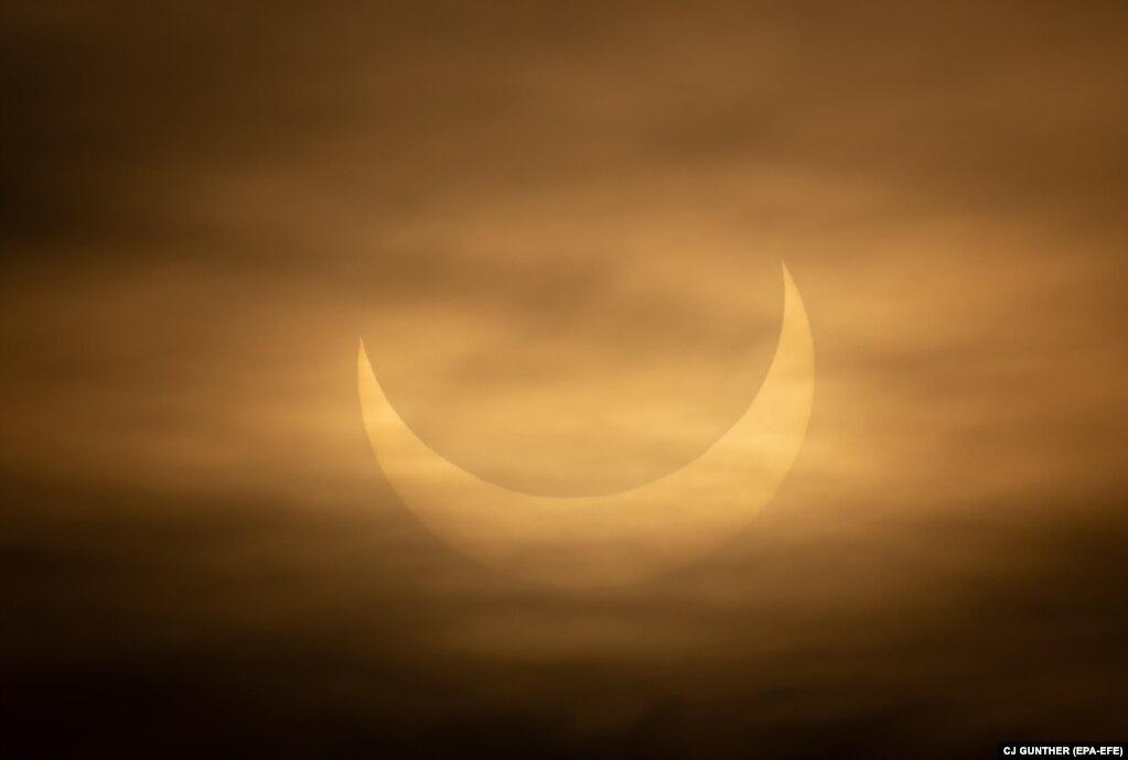 Затемнення видніється крізь хмари на сході сонця в Вінтропі, штат Массачусетс, США