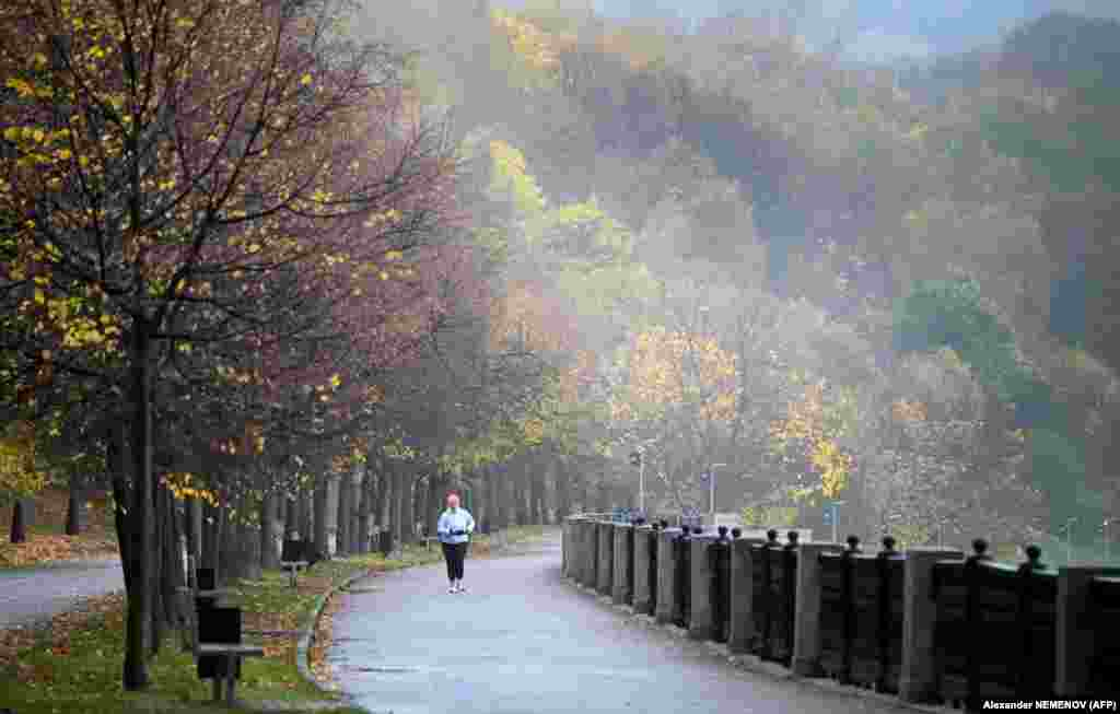 A woman runs along an embankment of the Moskva River in Moscow on October 16. (AFP/Alexander Nemenov)