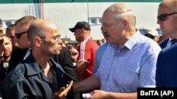 Belarusian President Alyaksandr Lukashenka (right) argues with a MZKT worker at the plant in Minsk on August 17.