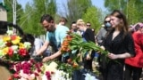 Mourners lay flowers at the grave of English teacher Elvira Ignatyeva, who was killed during a shooting at School No. 175, during her funeral in Kazan on May 12.
