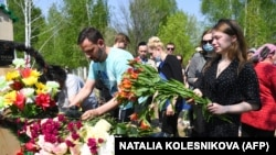 Mourners place flowers at the grave of English teacher Elvira Ignatyeva, who was killed during the shooting in Kazan, at her funeral on May 12.