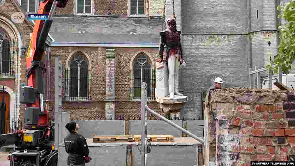 "A grab photograph of an handout video taken and released by the Belgian television channel ATV-ANTWERP TELEVISION on June 9, 2020 in Antwerp, shows city workers taking down the statue of late Belgian King Leopold II, a few days after it was daubed with paint by anti-racism protesters due the monarch brutal colonial ruling. Statues of Leopold have long been a target of activists because of his record in Belgium's African colonies, where he ran and exploited the then ""Congo Free State"" as a personal domain. The movement has gained momentum in recent days after the latest U.S. police killing of an unarmed black suspect triggered a global wave of protest."