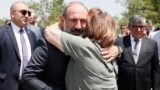 In a photo made available by the government, Armenian Prime Minister Nikol Pashinian is hugged by a woman at a burial place, on the outskirts of Yerevan, of Armenian soldiers killed during the Nagorno-Karabakh conflict.