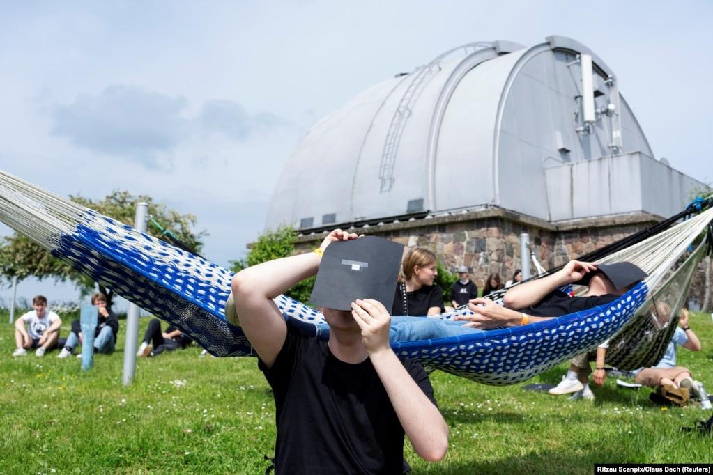 Чоловік спостерігає сонячне затемнення поблизу обсерваторії Брорфелле у Теллесе, Данія