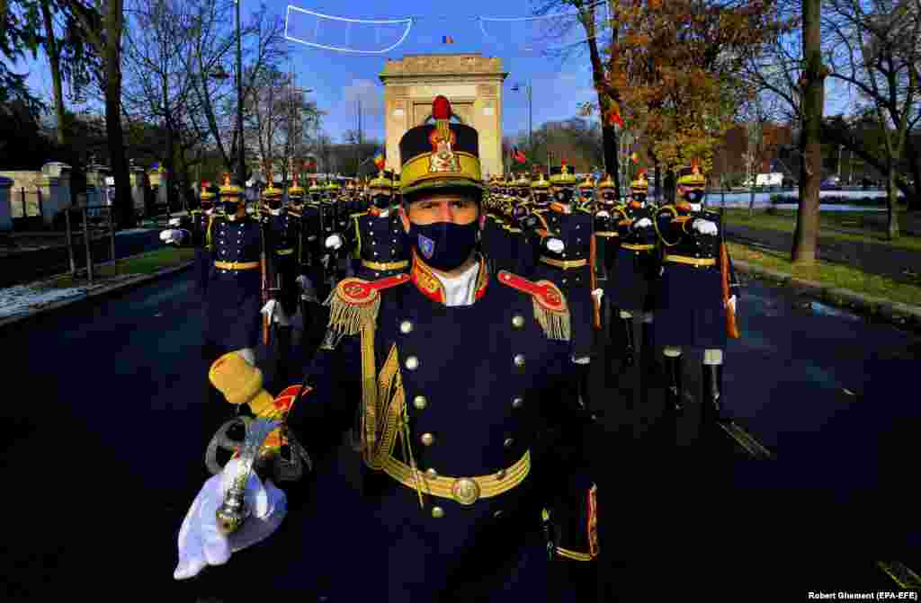 Soldiers from the Presidential Honor Guard wearing protective masks during a small ceremony to mark Romania's Great Union Day in Bucharest. (epa-EFE/Robert Ghement)